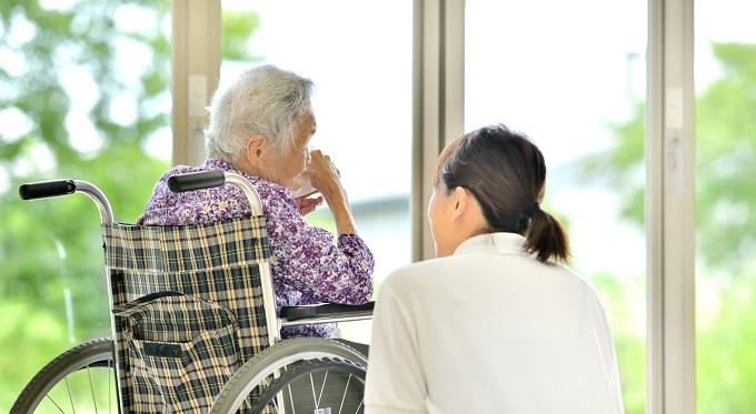 車いすの女性と話す介護士